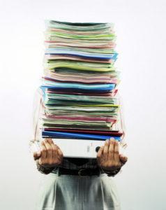 човек носи купчина папки с документи