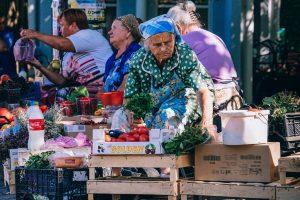 жена продава на пазар за плодове и зеленчуци